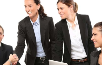 Varias personas con traje formal sentadas una mesa y estrechándose la mano