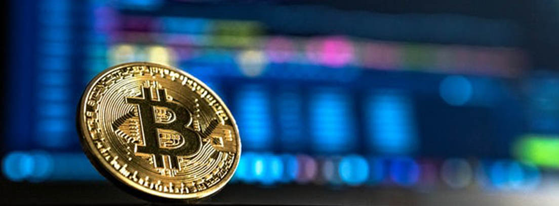 Moneda de bitcoin delante de gráficos