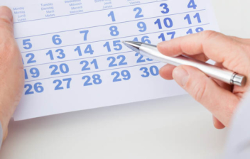 Hombre de espaldas señalando con un boli en un calendario sus vacaciones retribuidas y no disfrutadas