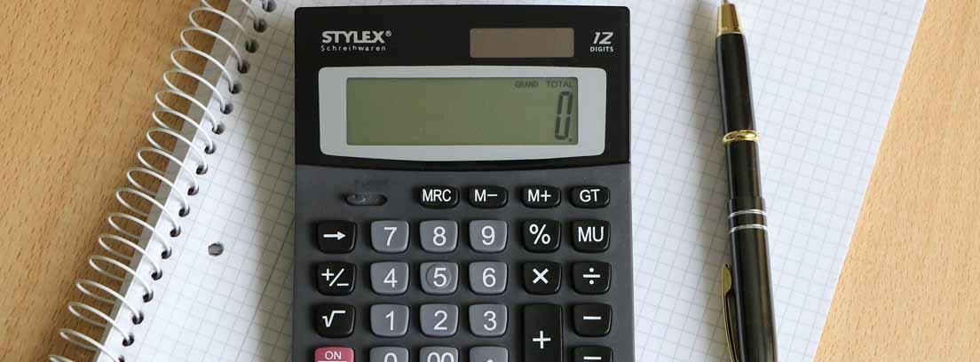 Vista cenital de una mesa con un cuaderno, un boli y una calculadora