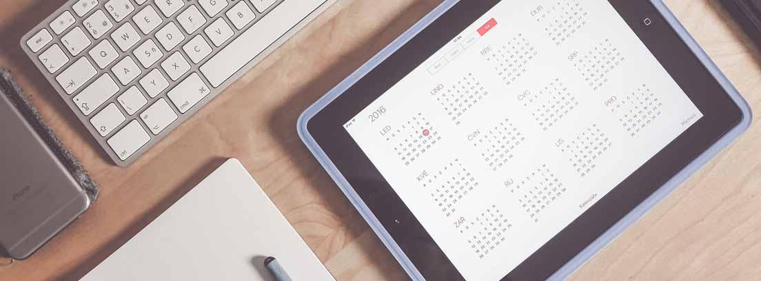 Vista cenital de una mesa con una teclado de ordenador, un cuaderno y un boli y una Tablet con un calendario de vacaciones retribuidas y no disfrutadas