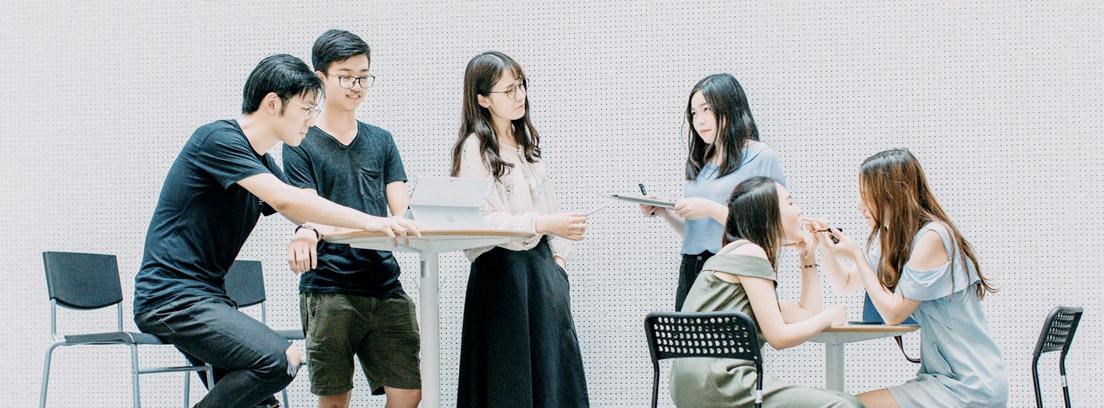 Varias personas entorno a mesa alta y otras sentadas en sillas