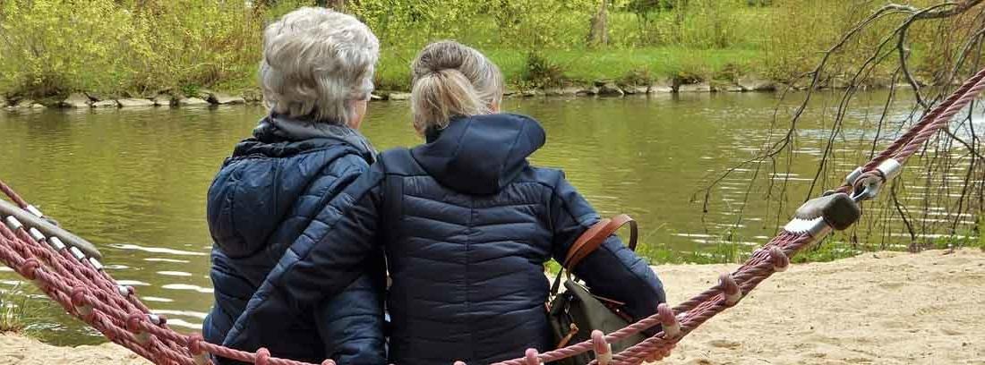 Dos personas mayores con pelo blanco sentadas en una hamaca
