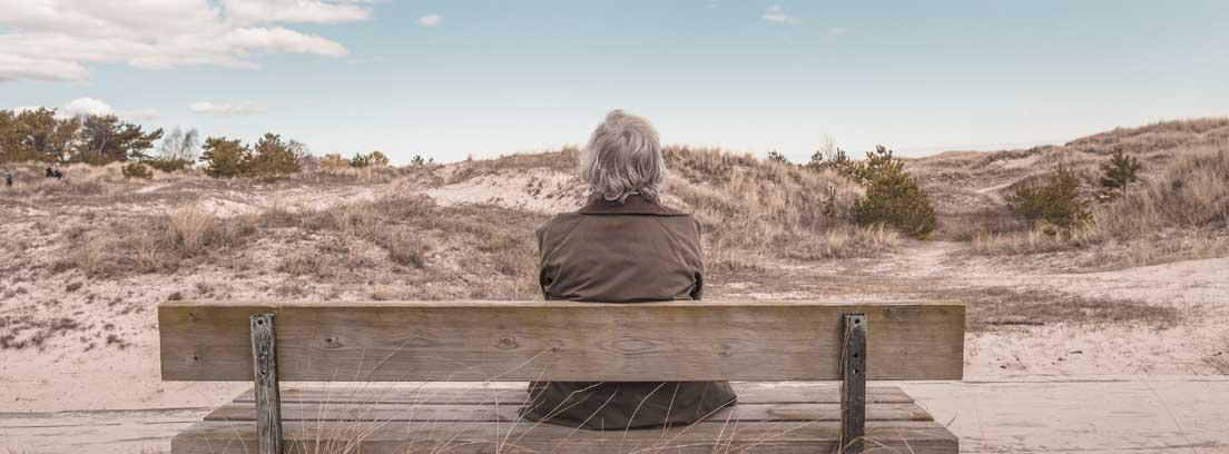 Mujer mayor de espaldas sentada en un banco disfrutando de la jubilación tras invertir en un plan de pensiones