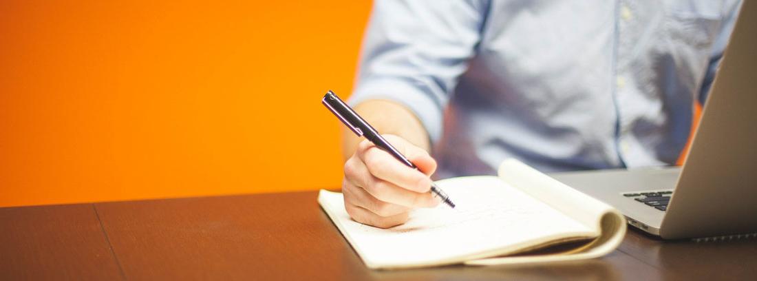 Hombre con un ordenador escribiendo en un cuaderno
