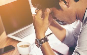 hombre mirando un informe sobre una mesa de trabajo
