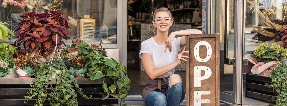 Mujer sonriente en la puerta de un negocio con un cartel de OPEN