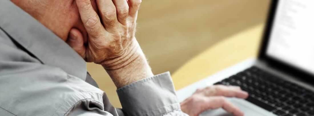Hombre mayor delante de un ordenador portátil