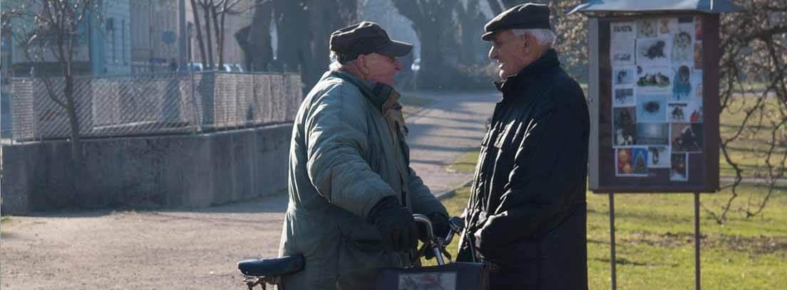 Dos hombres con pelo blanco y gorra hablan en la calle