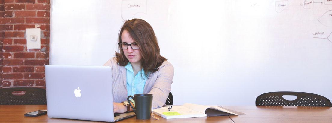 Mujer sentada a una mesa con un ordenador portátil trabajando con empresas de servicios digitales