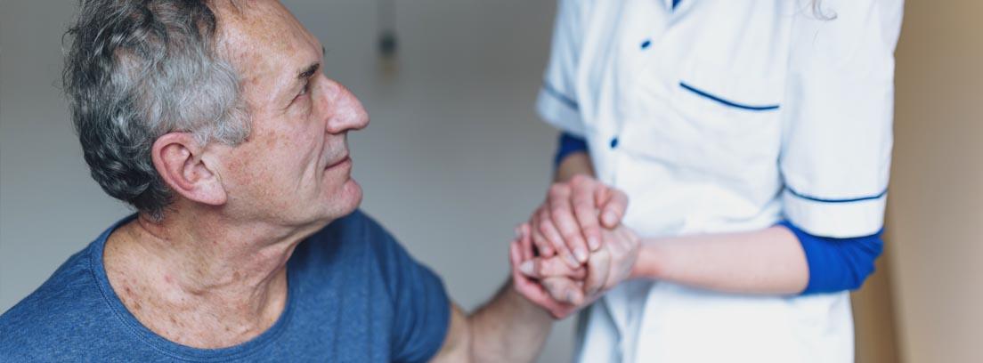hombre mayor dándole la mano a una enfermera