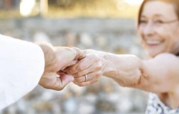Mujer mayor sujeta la mano de otra persona