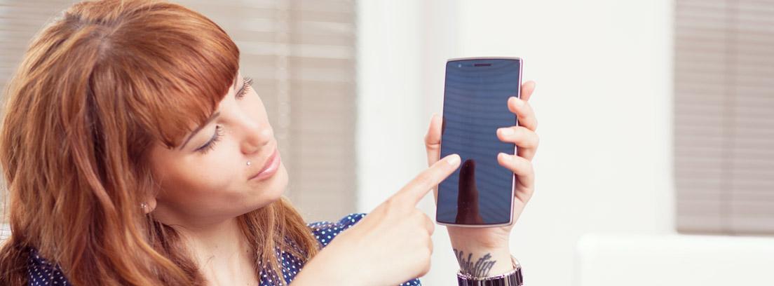 Mujer con móvil en la mano y dedo sobre la pantalla