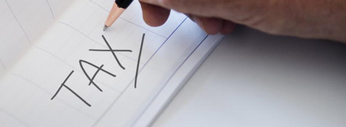 Mano sobre libreta con palabra Tax escrita