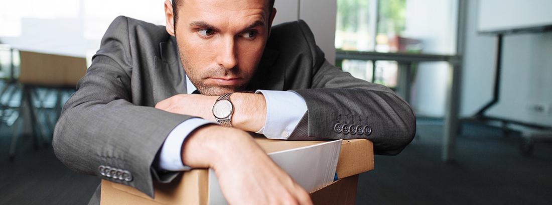 Hombre con gesto pensativo apoyado en una caja de cartón