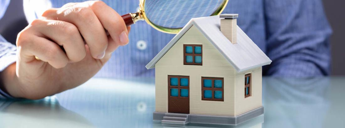 Hombre con lupa sobre una casa en miniatura