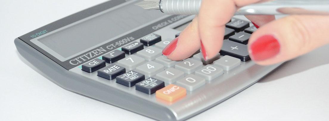 Mano sobre calculadora con pluma de escritura