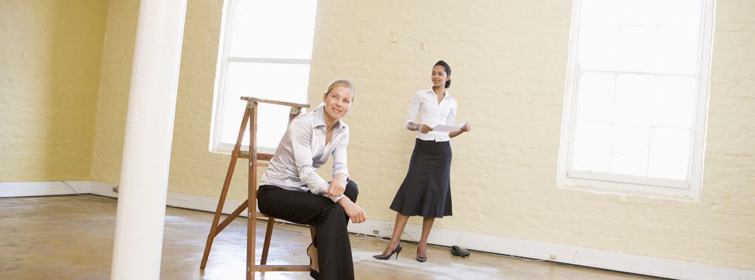 Una mujer de pie y otra sentada en una escalera en un local vacío