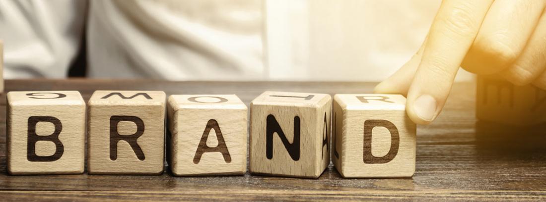 """Mano colocando bloques con letras formando la palabra """"Brand"""""""