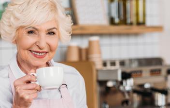 Mujer sonriente tomando una taza de café en su negocio disfrutando de una jubilación compatible con trabajo autónomo