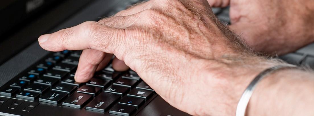 Manos ancianas sobre un teclado