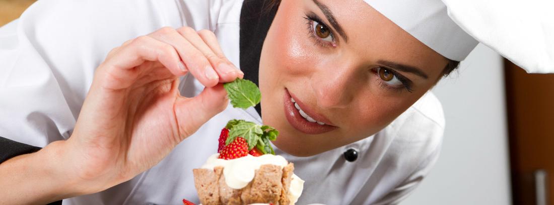 Mujer con chaqueta y gorro de chef colocando una hoja de menta en un postre