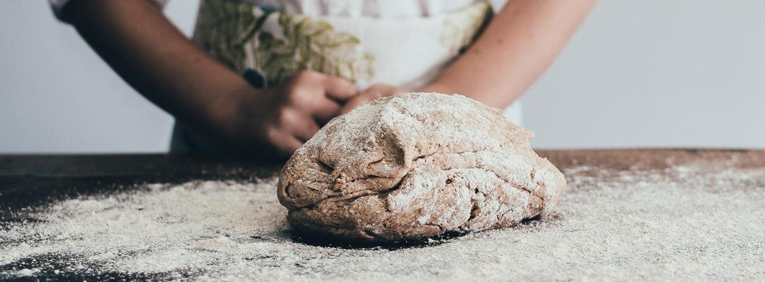 Hombre detrás de una mesa con la superficie enharinada y una bola de masa de pan