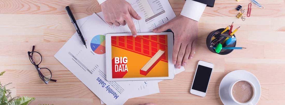 Vista cenital de unos brazos apoyados sobre una mesa con una Tablet en la que puede leerse Big Data, papeles, gafas, móvil y una taza de café