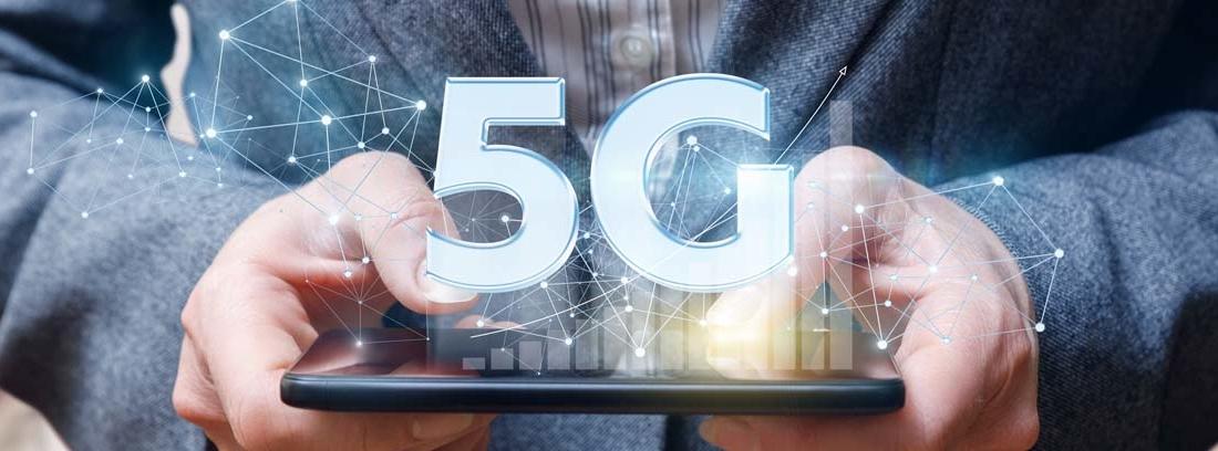 Manos de un hombre con traje sujetando un móvil con tecnología 5G