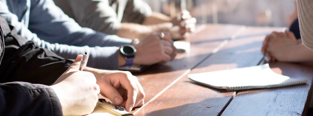 Diferentes personas con las manos sobre la mesa y papeles