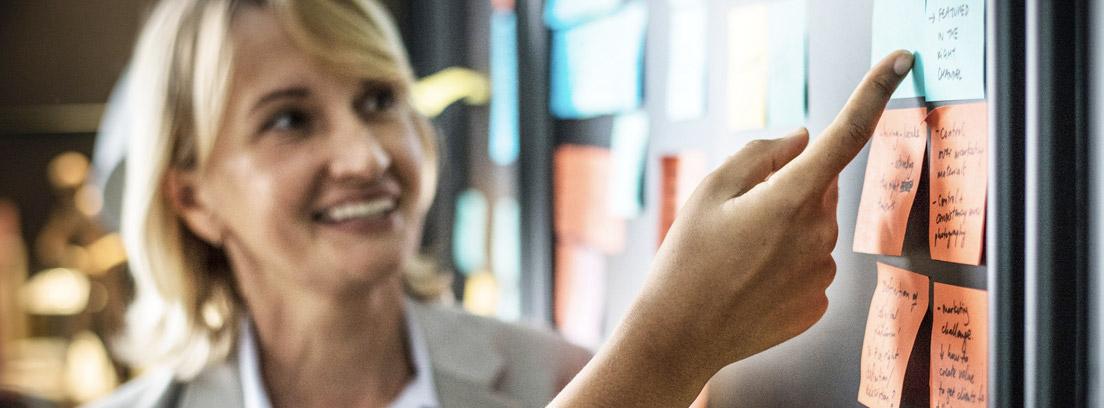 Mujer delante de un tablón con notas de colores
