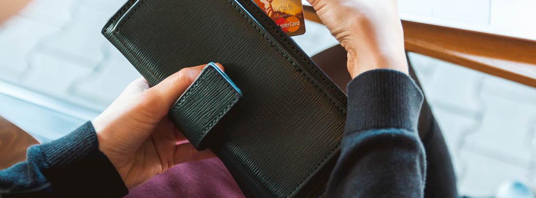 mujer sacando tarjeta de crédito para pagar una deuda con la Seguridad Social
