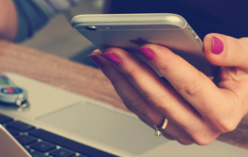 Manos de mujer sobre un ordenador portátil sujetando un móvil para pedir la vida laboral por SMS