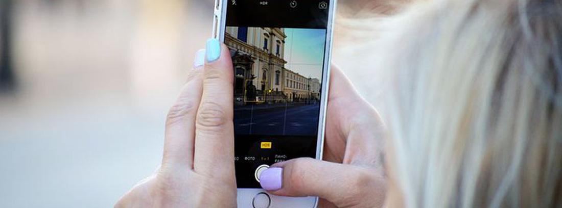 Mujer con móvil en la mano haciendo foto para subir a sus redes sociales
