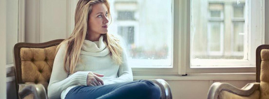 Mujer sentada con piernas dobladas en una butaca