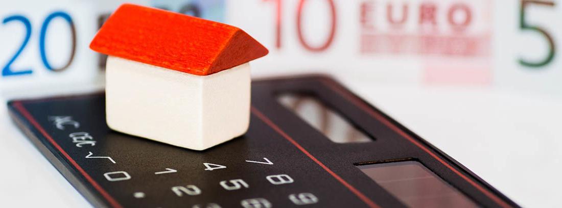 Maqueta de casa sobre calculadora y delante de billetes de euro