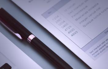 ordenador, bolígrafo y folio sobre una mesa