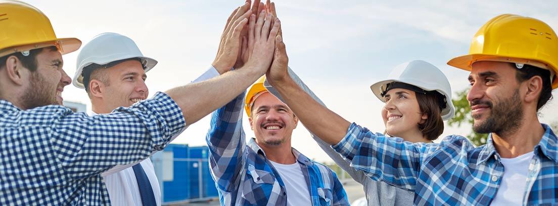 varios trabajadores chocando sus manos