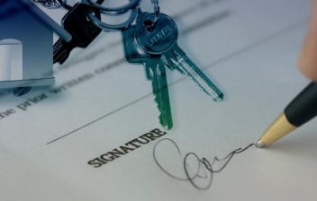 persona firmando una hipoteca y unas llaves sobre ella