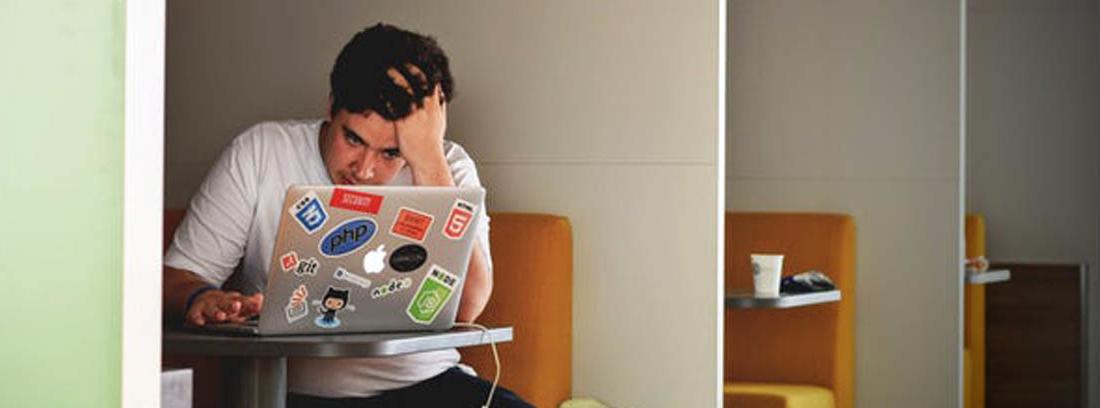 Persona sentada delante del ordenador con gesto preocupado
