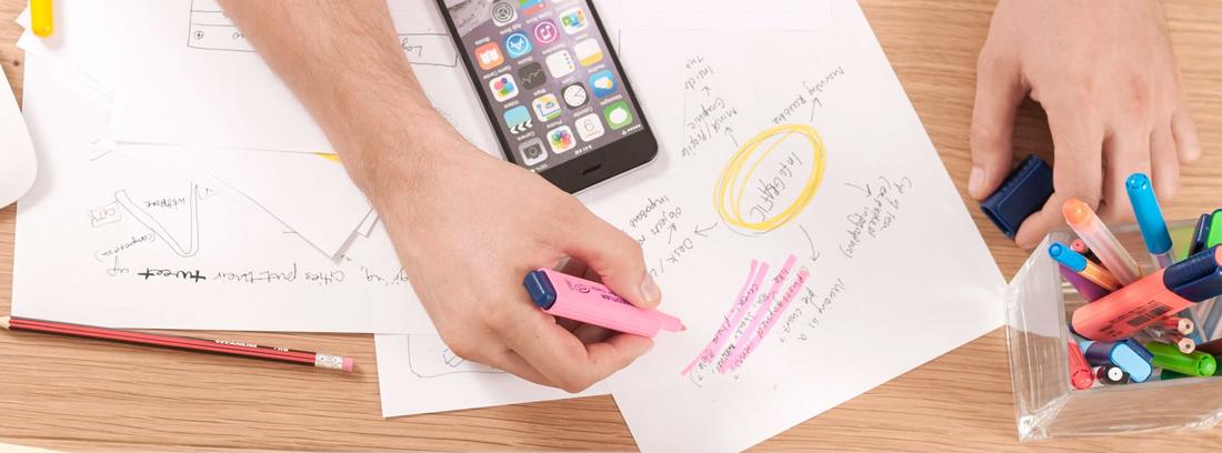 Manos con rotulador sobre papeles y junto al móvil