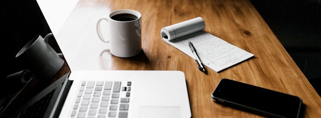 Ordenador portátil junto a taza, móvil y libreta con bolígrafo