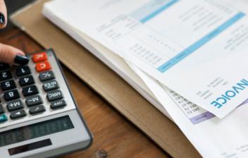 Mujer con calculadora y diferentes facturas en papel