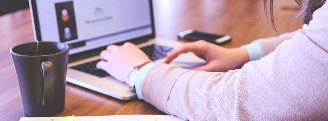 Persona con papeles y cuentas delante de ordenador portátil