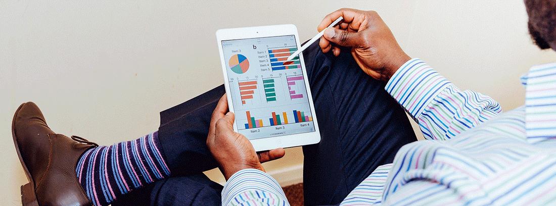 Hombre con tableta revisando gráficos económicos de su negocio