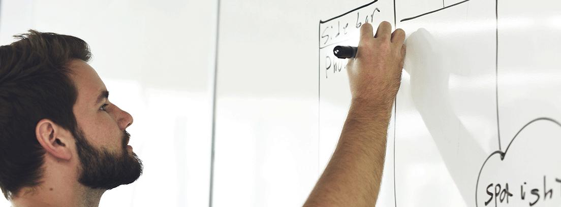 Hombre pintando sobre pizarra blanca de pared ideas para ahorrar