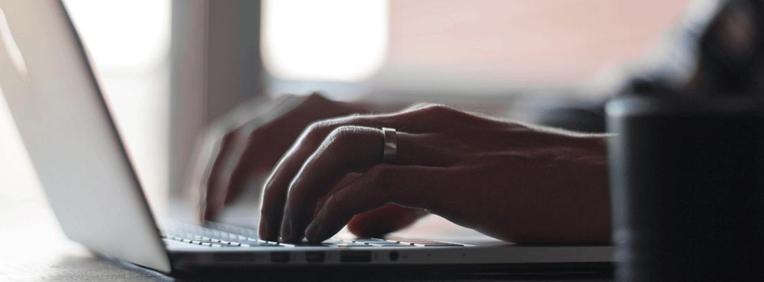 Manos sobre el teclado de un ordenador portátil para acceder a la banca online para mayores