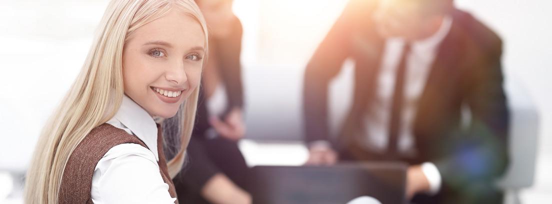 Mujer joven sonriente junto a dos hombres con un portátil