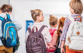 niños de espaldas con mochilas en el pasillo de un colegio