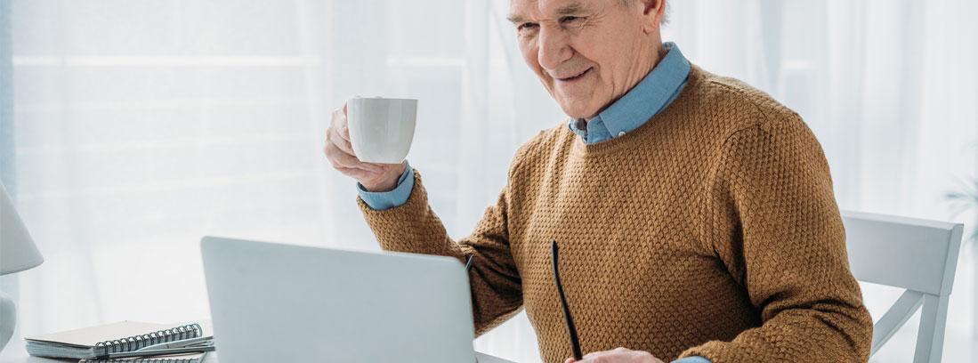 Hombre con pelo blanco delante de ordenador portátil